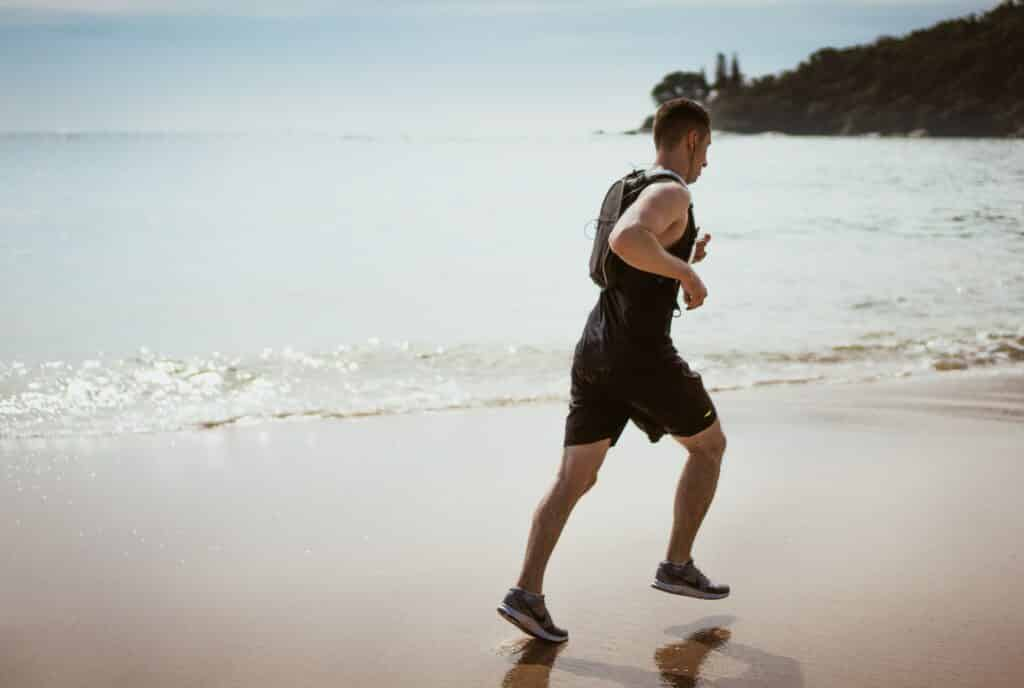 A man running on the beach after treatment with sports chiropractor josh french.