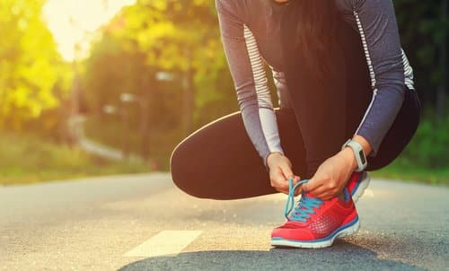Female runner tying her shoes before a run.